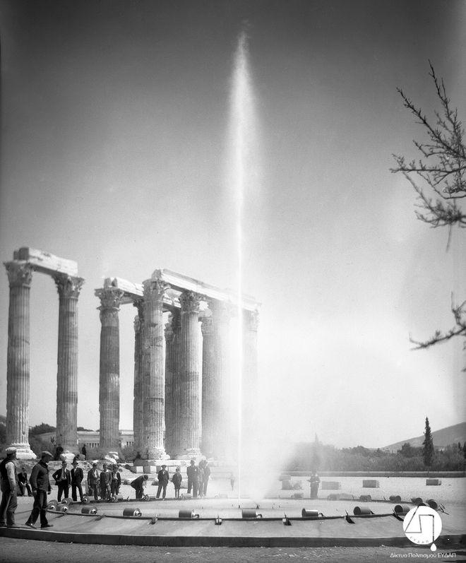 Στιγμιότυπο από την τελετή εγκαινίων του νέου δικτύου ύδρευσης των πόλεων Αθηνών, Πειραιώς και περιχώρων,  στους Στύλους του Ολυμπίου Διός, 03 Ιουνίου 1931.  Η Ελληνική Εταιρεία Υδάτων διαφημίζεται μέσω της τοποθέτησης πιδάκων νερού στην τελετή των εγκαινίων.