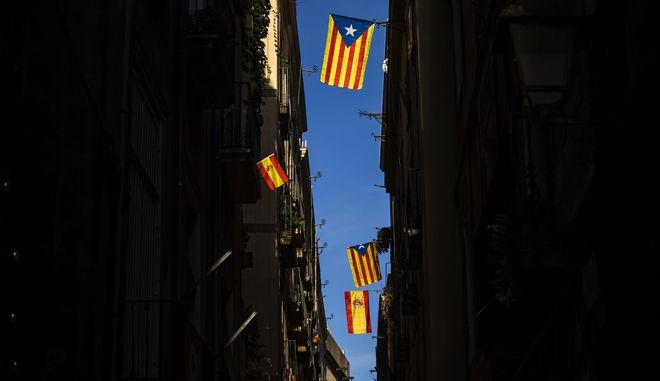 Esteladas or Independence flags and Spanish flags hang on balconies along a street in downtown Barcelona, Spain, Tuesday, Oct. 24, 2017. Catalonia's political leaders said Tuesday they are going to Spanish and international courts in an attempt to prevent Spain's government removing them from power and to proceed with their drive for the region's independence. (AP Photo/Emilio Morenatti)