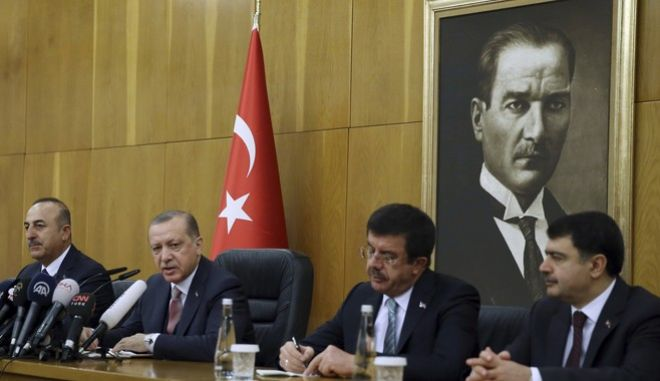 Turkish President Recep Tayyip Erdogan, second left, flanked by Foreign Minister Mevlut Cavusoglu, left, Economy Minister Nihat Zeybekci, second right, and Istanbul Gov. Vasip Sahin, speaks to the media before departing for a visit to Paris, in Istanbul, Friday, Jan. 5, 2018. Erdogan slammed the conviction in New York of a Turkish banker accused of helping Iran evade sanctions, saying the U.S. justice system poses a danger for the world. (Yasin Bulbul/Pool Photo via AP)