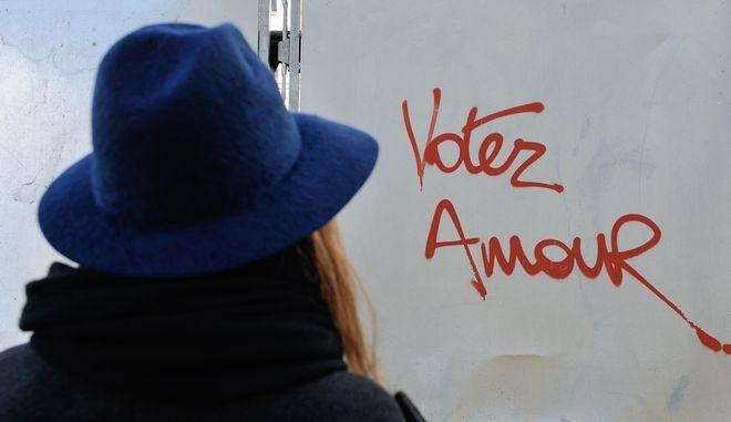 """Γυναίκα στο Παρίσι κοιτά ένα γκραφίτι που λέει """"Ψήφισε την αγάπη"""""""