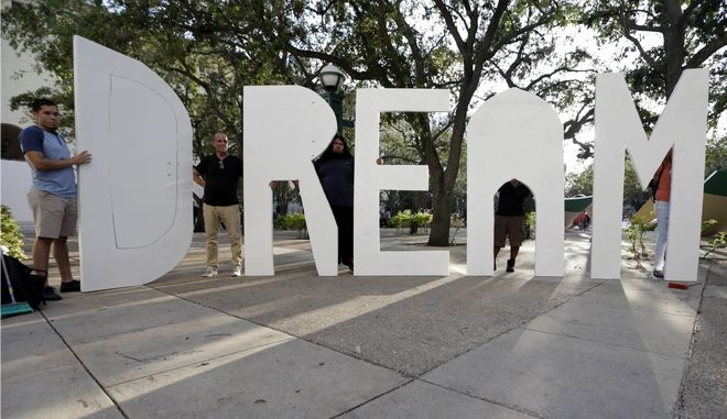 """Immigrant rights supporters hold giant letters reading """"Dream Act"""" as they demonstrate in favor of Congress passing a 'Clean Dream Act' that will prevent the deportation of young immigrants known as Dreamers working and studying in the U.S.,Friday, Oct. 13, 2017, in Miami. President Trump announced plans to end a program protecting them. (AP Photo/Lynne Sladky)"""