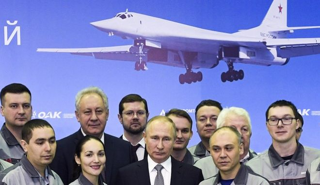 Russian President Vladimir Putin, center, poses for a photo with employees as he visits an aircraft making plant in Kazan, Russia, Thursday, Jan. 25, 2018. Putin watched a demonstration flight of a Tu-160 strategic bomber and met with workers. (Alexei Nikolsky, Sputnik, Kremlin Pool Photo via AP)