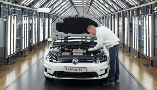 Rainer Jopp makes the final check of an e-Golf electric car in the so-called light tunnel during the official production start in the German car manufacturer Volkswagen Transparent Factory (Glaeserne Manufaktur) in Dresden, eastern Germany, Monday, April 3, 2017. (AP Photo/Jens Meyer)