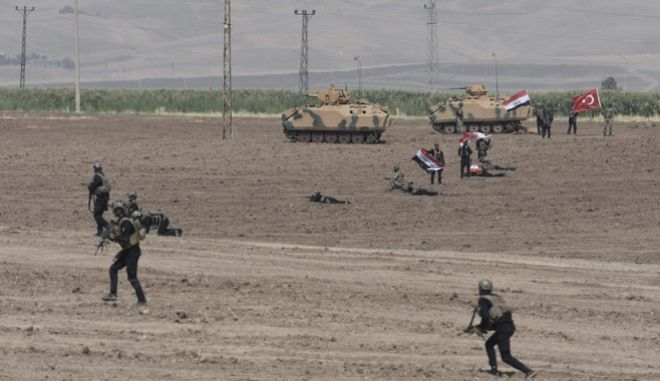 Turkish and Iraqi soldiers walk with Turkish tanks during the exercises in Silopi, near the Habur border gate with Iraq, southeastern Turkey, Tuesday, Sept. 26, 2017. Tanks with soldiers holding the Turkish and Iraqi flags rolled on a field lifting up dust, as the two countries' militaries conducted joint exercises on Turkey's border with Iraq's semi-autonomous Kurdish region.(DHA-Depo Photos via AP )