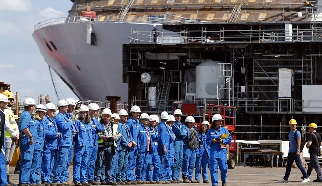 STX workers gather before a visit by French President Emmanuel Macron at the STX shipyard site in Saint-Nazaire, western France, Wednesday, May 31, 2017. With a capacity of 65700 passengers and 1550 crew members, the MSC Meraviglia, on background, is the biggest cruise ship in Europe. (Stephane Mahe/Pool Photo via AP)