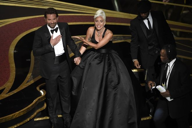 Bradley Cooper, left, and Lady Gaga react to the audience after a performance of