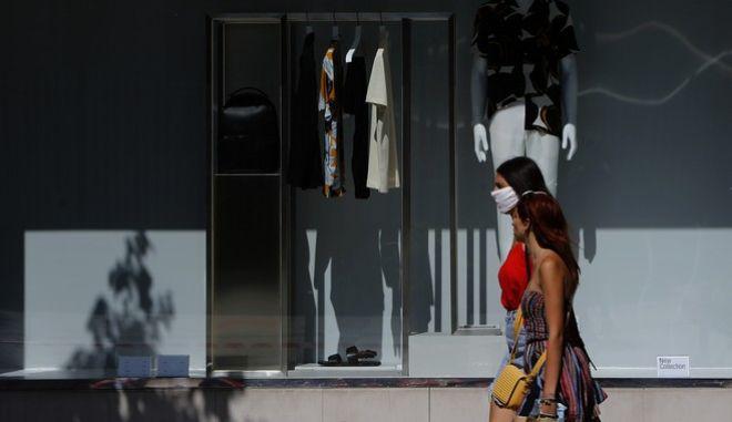 Άνθρωποι με μάσκα κατά του κορονοϊού περπατούν σε δρόμο της Κύπρου