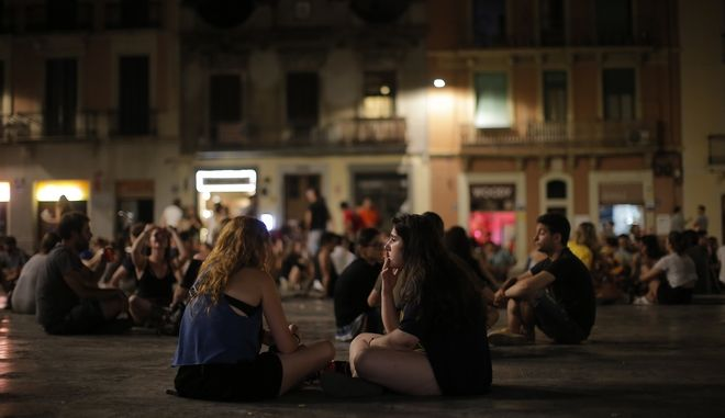 People enjoy a night of summer weather at the Gracia neighborhood in Barcelona, Spain, Tuesday, Aug. 2, 2016.  Temperatures in Barcelona climbed to 26 degrees Celsius (78 Fahrenheit). (AP Photo/Manu Fernandez)
