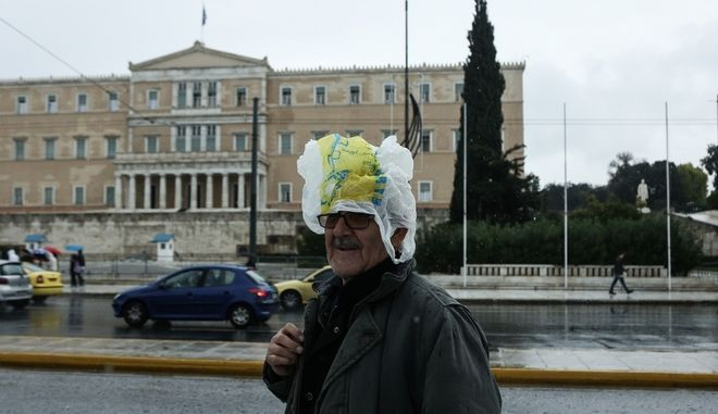 An elderly man covers his head with a nylon bag, to protect himself from the rain, in Syntagma Square, Athens, December 10, 2014 /                ,   , , 10 , 2014