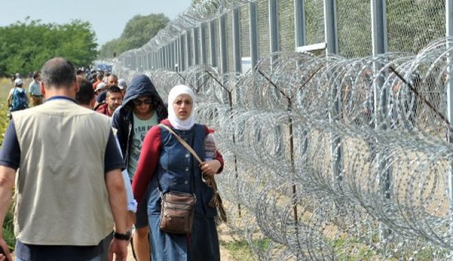 """Migrants and refugees walk near razor-wire along a 3-meter-high fence at the official border crossing between Serbia and Hungary, near the northern Serbian town of Horgos on September 15, 2015. Hungary effectively sealed its border with Serbia on September 15 to stem the massive influx of refugees as Germany slammed the """"disgraceful"""" refusal of other EU countries to accept more migrants after 22 died in yet another shipwreck. AFP PHOTO / ELVIS BARUKCIC"""