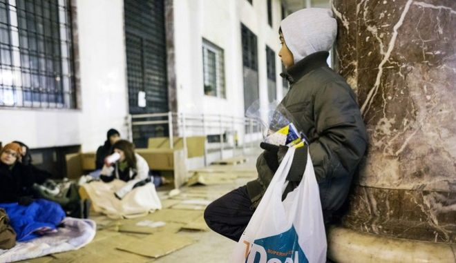 A child who sells tissues in the street, looks the volunteers. Members of voluntary organizations sleeping in Aristotle Square in solidarity with homeless people on December 5, 2012 World Day of Volunteering in the northern Greece city of Thessaloniki./       ,   .             ,  5   2012   , .