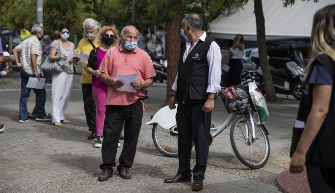 Άνθρωποι με μάσκες αναμένουν να εξεταστούν από Κινητή Ομάδα του ΕΟΔΥ