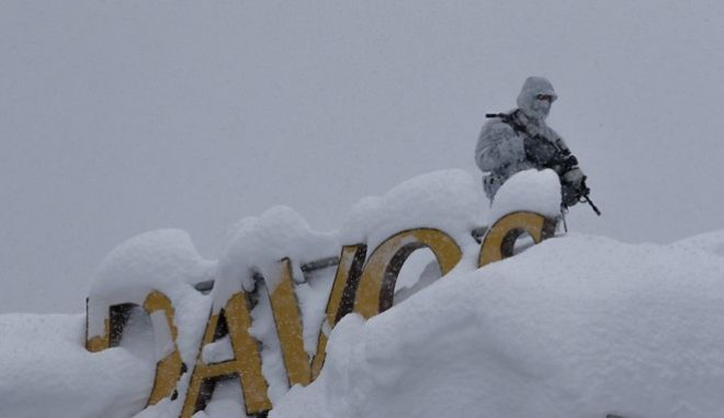 An armed Swiss police officer stands guard on the roof of a hotel near the congress center where the annual meeting of the World Economic Forum take place in Davos, Monday, Jan. 22, 2018. The meeting brings together entrepreneurs, scientists, chief executives and political leaders from Jan. 23 to 26. (AP Photo/Markus Schreiber)