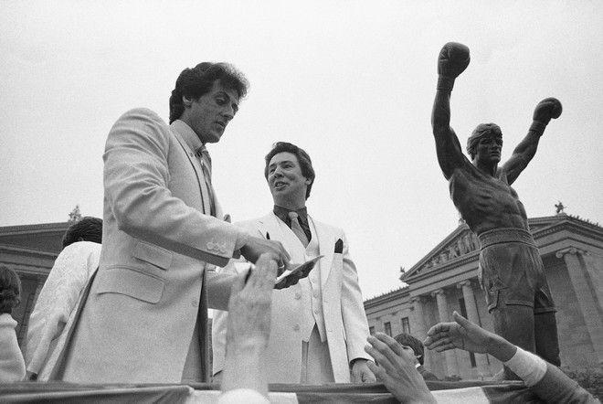Ο Σιλβέστερ Σταλόνε υπογράφει αυτόγραφα κατά την επίσημη τελετή τοποθέτησης του αγάλματος του Ρόκι στα σκαλιά του Μουσείου Τέχνης της Φιλαδέλφειας. Η φωτογραφία τραβήτηκε στις 25 ΜαΪου 1982.