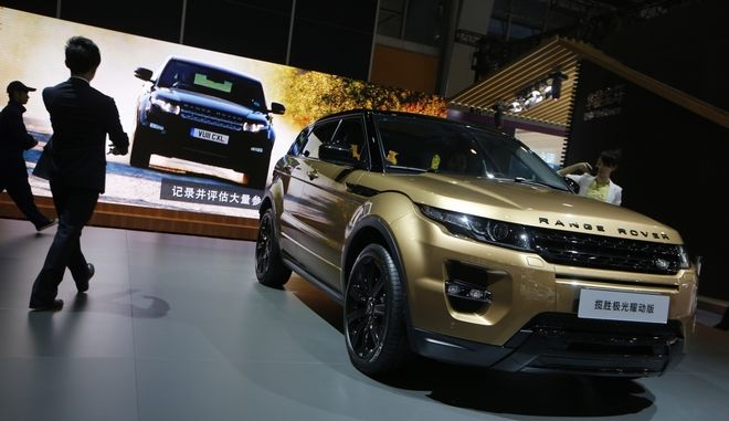 Visitors walk besides the Range Rover Evoque Dynamic at the company's booth during Guangzhou 2013 Auto Show in China's southern city of Guangzhou,Thursday, Nov. 21, 2013.  (AP Photo/Kin Cheung)