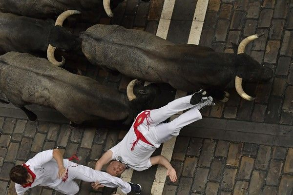 A reveller falls in front of Jose Escolar fighting bulls during the second running of the bulls at the San Fermin Festival, in Pamplona, northern Spain, Saturday, July 8, 2017. Revellers from around the world flock to Pamplona every year to take part in the eight days of the running of the bulls. (AP Photo/Alvaro Barrientos)