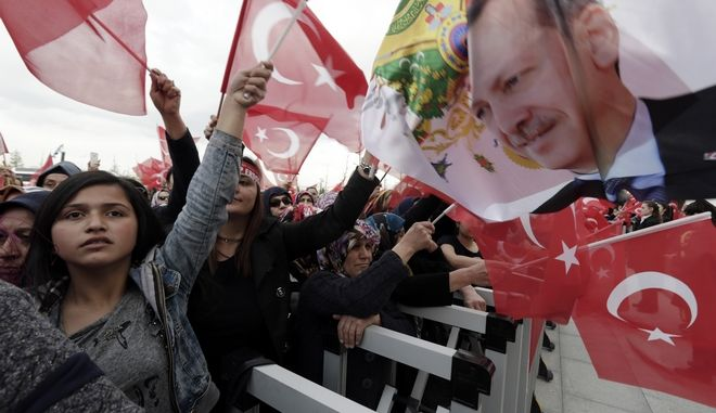 Supporters wave flags as Turkey's President Recep Tayyip Erdogan delivers a speech during a rally of supporters a day after the referendum, at his palace, in Ankara, Turkey, Monday, April 17, 2017. Turkey's main opposition party urged the country's electoral board Monday to cancel the results of a landmark referendum that granted sweeping new powers to Erdogan, citing what it called substantial voting irregularities. (AP Photo/Burhan Ozbilici)