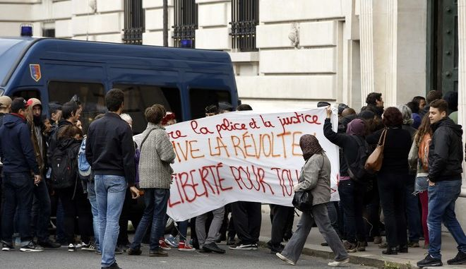 "Youths carry a banner reading ""Against police and justice, long live the revolt, freedom for all"" outside the Paris hall of justice, Wednesday, Oct.11, 2017. Seven people accused of launching a vicious attack on a police car in Paris last year have been handed prison sentences up to seven years. (AP Photo/Thibault Camus)"