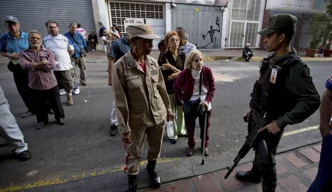 Voters flanked by Venezuelan Bolivarian National guards soldiers wait to enter a poll station during Venezuelan mayoral elections in Caracas, Venezuela, Sunday, Dec. 10, 2017. Venezuelans will choose hundreds of mayors on Sunday in elections pitting candidates backed by President Nicolas Maduro against a fractured opposition still bruised by a poor showing in recent gubernatorial voting.(AP Photo/Fernando Llano)