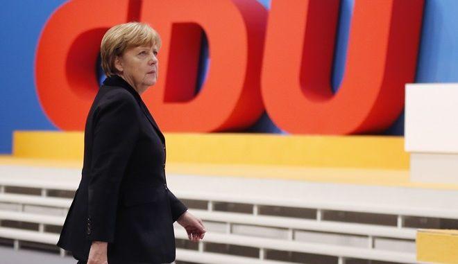 Η Άγγελα Μέρκελ περπατά μπροστά από το σήμα του κόμματος CDU