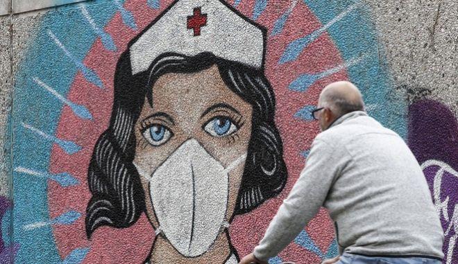 Άνδρας περνά μπροστά από γκράφιτι για την πανδημία