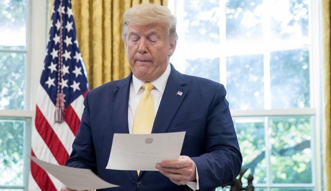 Ο Ντόναλτ Τραμπ κοιτάζει έγγραφα στο Οβάλ Γραφείο