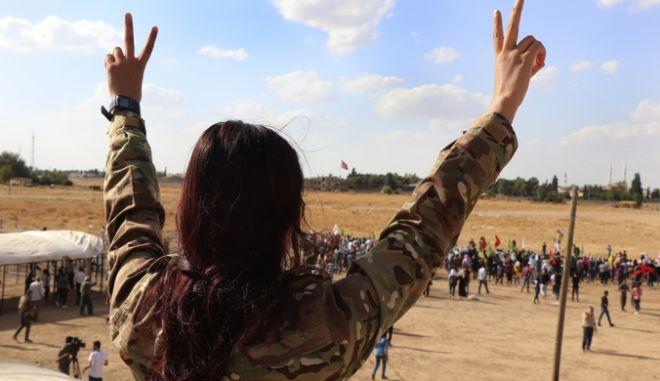 Κούρδισσα μαχήτρια σχηματίζει το σήμα της νίκης