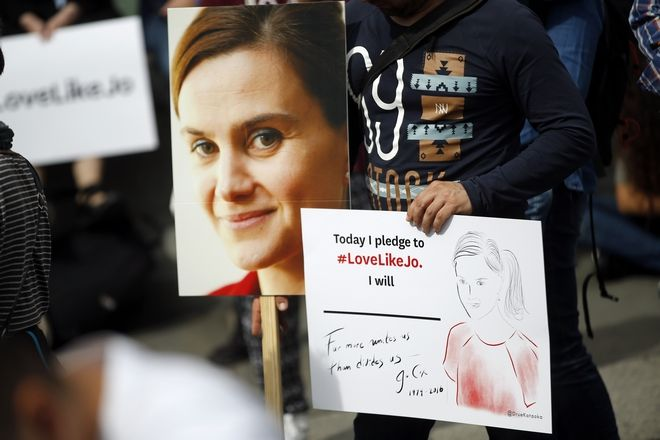 People hold signs during a gathering to celebrate the life of murdered British MP Jo Cox, near the River Thames in London, Wednesday, June 22, 2016. Jo Cox, a 41-year-old Labour lawmaker who had championed the cause of Syrian refugees, was stabbed and shot to death outside a library in her northern England constituency on Thursday. The suspect gave his name in court as