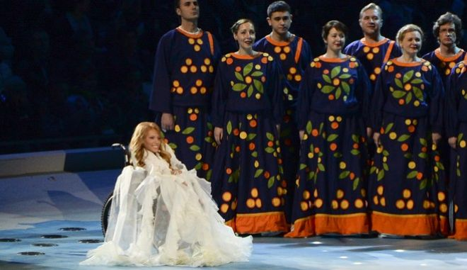 """In this photo taken on Friday, March 7, 2014, Yulia Samoylova sings during the opening ceremony of the 2014 Paralympic Games in Sochi, Russia. Russian broadcaster Channel One announced on Sunday March 12, 2017, that 27-year old Yulia Samoylova, who has used a wheelchair since childhood, would represent Russia at the Eurovision contest with the song """"Flame is Burning"""". (AP Photo/Ekaterina Lyzlova)"""