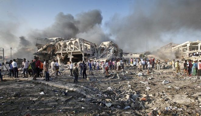 Somalis gather and search for survivors by destroyed buildings at the scene of a blast in the capital Mogadishu, Somalia, Saturday, Oct. 14, 2017. A huge explosion from a truck bomb has killed at least 20 people in Somalia's capital, police said Saturday, as shaken residents called it the most powerful blast they'd heard in years. (AP Photo/Farah Abdi Warsameh)
