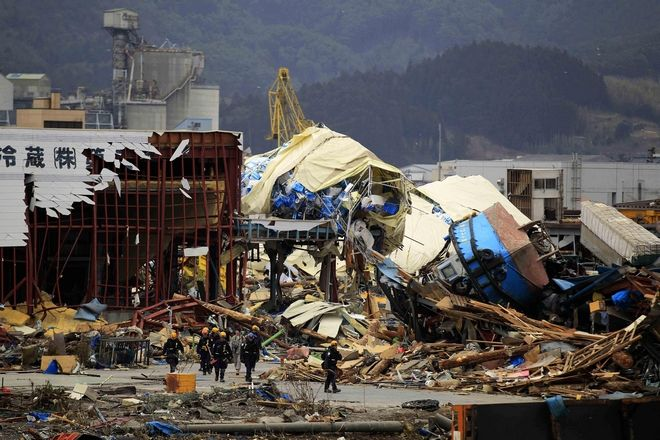 Members of a Los Angeles County in the U.S. search and rescue team walk past an upside ship washed ashore by the tsunami in Ofunato, Japan, Tuesday, March 15, 2011. Two search and rescue teams from the U.S. and a team from the U.K. with combined numbers of around 220 personnel have arrived in northern Japan to help in the aftermath of the earthquake and tsunami. (AP Photo/Matt Dunham)