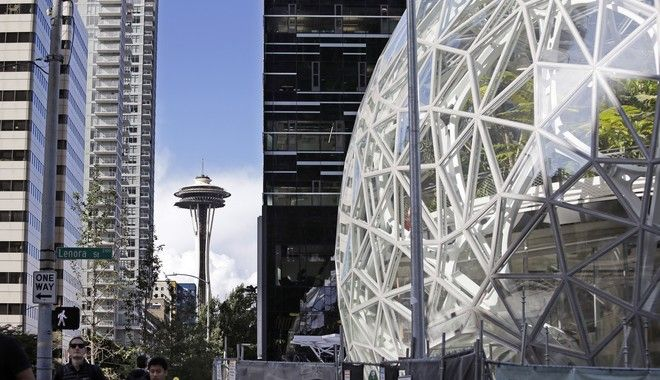 In this Wednesday, Oct. 11, 2017, photo, large spheres take shape in front of an existing Amazon building and in view of the Space Needle in Seattle. A huge spike in housing prices, traffic snarling downtown, long-time residents and businesses displaced. The dozens of North American cities vying to become Amazons second home are focused on the positives of luring the tech giant. But many in Seattle say Amazons explosive growth has not been without a significant downside in its birthplace. (AP Photo/Elaine Thompson)