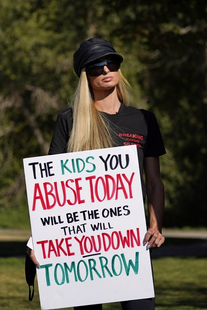 Paris Hilton holds a sign before leading a protest Friday, Oct. 9, 2020, in Provo, Utah. Hilton was in Utah Friday to lead a protest outside a boarding school where she alleges she was abused physically and mentally by staff when she was a teenager. Hilton, now 39, went public with the allegations in a new documentary and wants a school that she says left her with nightmares and insomnia for years to be shut down. (AP Photo/Rick Bowmer)