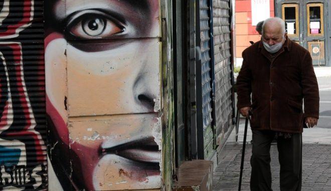 Ηλικιωμένος άνδρας περπατά στο κέντρο της Αθήνας