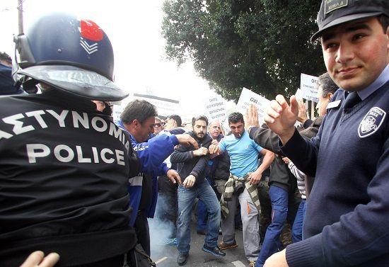 Με πλαστικά μπουκάλια νερού και φρούτα, εργαζόμενοι στην Αρχή Ηλεκτρισμού Κύπρου, οι οποίοι συμμετέχουν στη διαδήλωση έξω από τη Βουλή των Αντιπροσώπων, προσπαθούν να εισέλθουν εντός του κτιρίου. Εκατοντάδες εργαζόμενοι φωνάζοντας