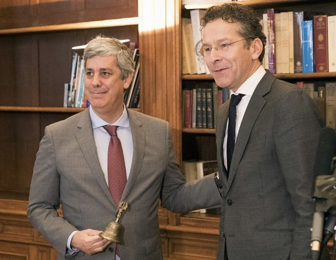 Outgoing leader Jeroen Dijsselbloem, right, of the Netherlands formally hands over power of the so-called eurogroup, in the form of a symbolic bell, to Portugal's Mario Centeno during a ceremony in Paris, Friday, Jan.12, 2018. The euro zone's new leader says he hopes to use his term to bring the 19 countries that use the currency closer together and toughen their ability to weather future crises. (AP Photo)