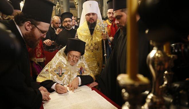 Ο Οικουμενικός Πατριάρχης Βαρθολομαίος υπογράφει τον τόμο που παραχωρεί Αυτοκεφαλία στην Εκκλησία της Ουκρανίας παρουσία του προέδρου της Ουκρανίας Πέτρο Ποροσένκο.