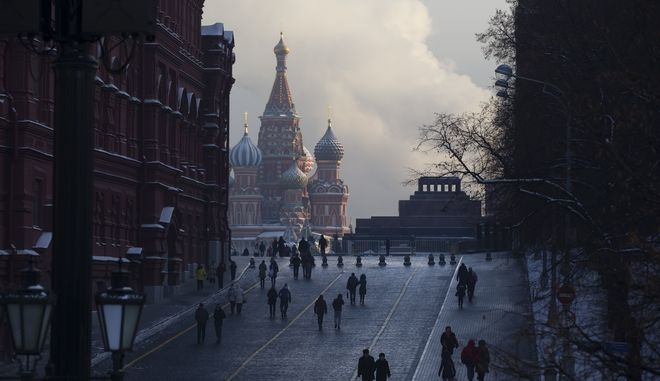 People walk to Red Square shrouded in cold mist, with the St. Basil's Cathedral, center, and Lenin mausoleum, right, in Moscow, Monday, Jan. 9, 2017. The temperature plunged to minus -21 Celsius (minus-6 F). (AP Photo/Alexander Zemlianichenko)