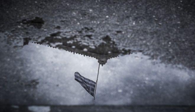 Η σημαία της Βουλής ανακλάται στο νερό της βροχής που έχει συγκεντρωθεί στο δρόμο