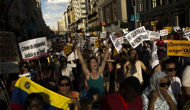 """People shout slogans during a protest demanding the Spanish government fulfill its pledge to give shelter to refugees, in Madrid, Saturday, June 17, 2017. A few thousand protesters marched in Madrid on Saturday to urge Spain's conservative government to fulfill its pledge to give shelter to refugees from war-torn countries like Syria. Placards read in Spanish: """"No wars, neither borders"""", """"We want to give shelter now!"""", """"Crime of inhumanity"""". (AP Photo/Francisco Seco)"""