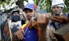 FILE - In this July 26, 2017 file photo, Wuilly Arteaga, whose face shows signs of injury, plays his violin during clashes with Venezuelan Bolivarian National Guards on the first day of a 48-hour general strike in protest of government plans to rewrite the constitution, in the Bello Campo neighborhood of Caracas, Venezuela. The violinist who has become a well-known face of anti-government protests was freed after more than two weeks in prison, according to the nations chief prosecutor on Tuesday, Aug. 15, 2017. (AP Photo/Ariana Cubillos, File)