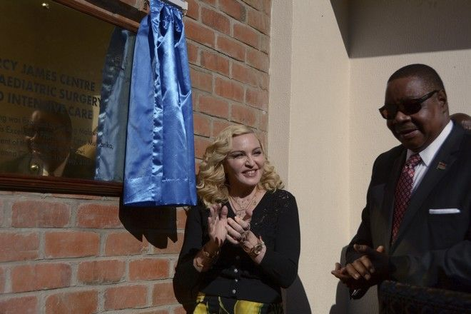 Pop star Madonna, left, and Malawian President Peter Mutharika, unveil a plaque at the opening of The Mercy James Institute for Pediatric Surgery and Intensive Care, at the Queen Elizabeth Central Hospital in the city of Blantyre, Malawi, Tuesday, July 11, 2017.  The children's wing facility is named after Madonna's adopted child 11-year-old  Mercy James and building funded by her charity Raising Malawi in collaboration with Malawi's health ministry. (AP Photo / Thoko Chikondi)