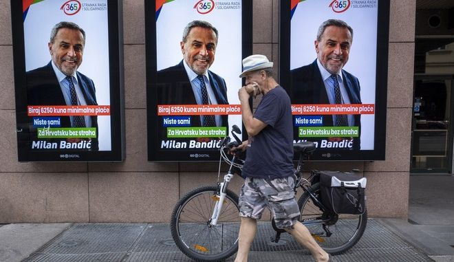 A man walks past electoral posters of Zagreb's mayor Milan Bandic, in Zagreb, Croatia, Thursday, July 2, 2020. Croatia is holding a parliamentary election on July 5, 2020, with no clear winner in sight as the ruling conservatives' bid for re-election faces a strong challenge from both liberal and right-wing groups. (AP Photo/Sasa Kavic)
