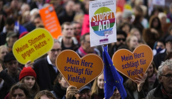 Thousands of people attend a demonstration with the slogan 'Against Hate and Racism at the Bundestag' in Berlin, Sunday, Oct. 22, 2017. The new elected German parliament Bundestag will  for its first session on Tuesday, Oct. 24, 2017. The German language posters read:'Stop AfD' (Alternative for Germany), 'My voice against hate, and 'Against racism in the Bundestag'. (AP Photo/Markus Schreiber)
