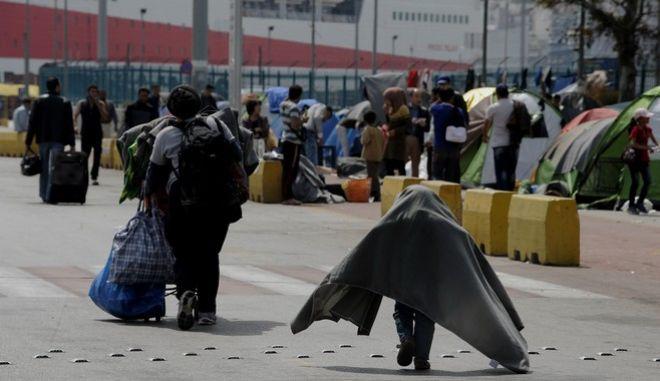 Από νωρίς το πρωί στην πύλη Ε1 στο λιμάνι του Πειραιά,κλιμάκιο της Ύπατης αρμοστείας του ΟΗΕ για τους πρόσφυγες και του Υπουργείου μεταναστευτικής πολιτικής με διερμηνείς,ενημέρωναν τους μετανάστες και του πρόσφυγες που βρίσκονται εκεί για το κλείσιμο του πρόχειρου καταυλισμού. Οι επιλογές ήταν δυο,η μεταφορά τους σε κέντρο φιλοξενίας στην Πέτρα του Ν.Κατερίνης(μοιράστηκαν και φωτογραφίες από τις εγκαταστάσεις εκεί) ή στην πύλη Ε1.Οι περισσότεροι προτίμησαν να μετακινηθούν στην πύλη Ε1 με λεωφορεία του ΟΛΠ,καθώς δεν επιθυμούν να απομακρυνθούν από τον Ν.Αττικής,κάποιοι (οι λιγότεροι)αργά το μεσημέρι αναχώρησαν με πούλμαν(το ένα με 45άτομα)με προορισμό την Κατερίνη,Πέμπτη 7 Απριλίου 2016 (EUROKINISSI/ΤΑΤΙΑΝΑ ΜΠΟΛΑΡΗ)