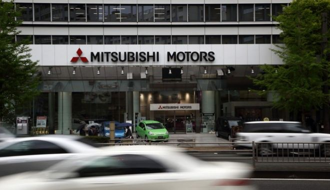 Traffic moves past Mitsubishi Motors Corp. Mirage vehicles displayed outside the company's headquarters in Tokyo, Japan, on Wednesday, April 24, 2013. Mitsubishi Motors plans to increase production at the company's Mizushima plant in western Japan, according to a statement. Photographer: Tomohiro Ohsumi/Bloomberg