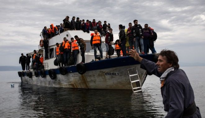 Around 200 refugees and migrants arrive in a fishing boat on the Greek island of Lesbos after crossing the Aegean sea from Turkey, on October 11, 2015 /  200                   ,  ,  11 , 2015