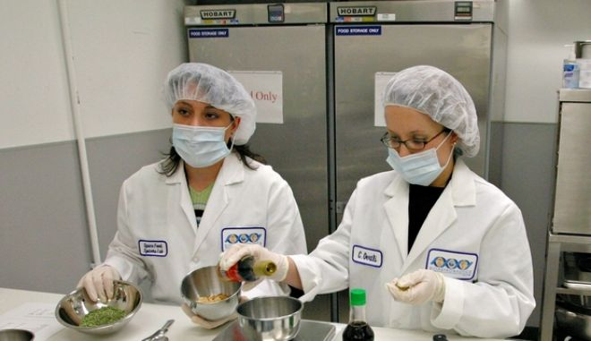 NASA Food Scientists Donna Nabors, left, and Connie Oertli, right, show journalists how they prepare freeze dried fried rice in the Space Food Systems Laboratory at Johnson Space Center in Texas, Wednesday, Nov. 19, 2003.  Tang and dry meal cubes are no longer on the menu for astronauts. While orbiting the earth, scientists can dine on shrimp cocktail, chicken fajitas or chocolate pudding cake. (AP Photo/Michael Stravato)