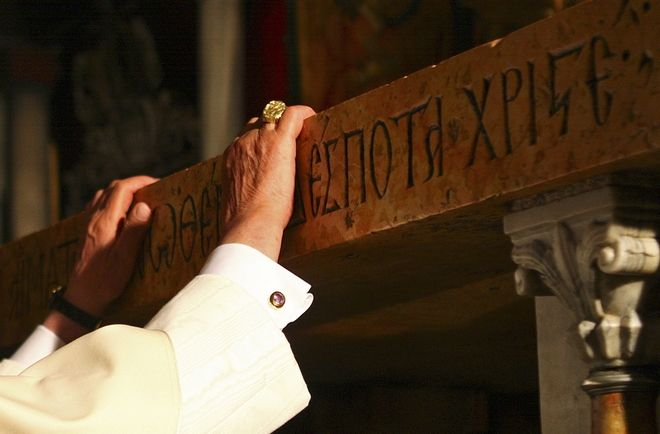 Pope Benedict XVI touches the traditional site where Jesus was crucified in the Golgotha, or Calvary, at the Church of the Holy Sepulcher in Jerusalem's Old City, Friday, May 15, 2009