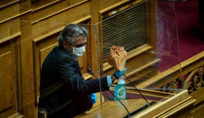 Ύπάλληλος της Βουλής καθαρίζει το προστατευτικό